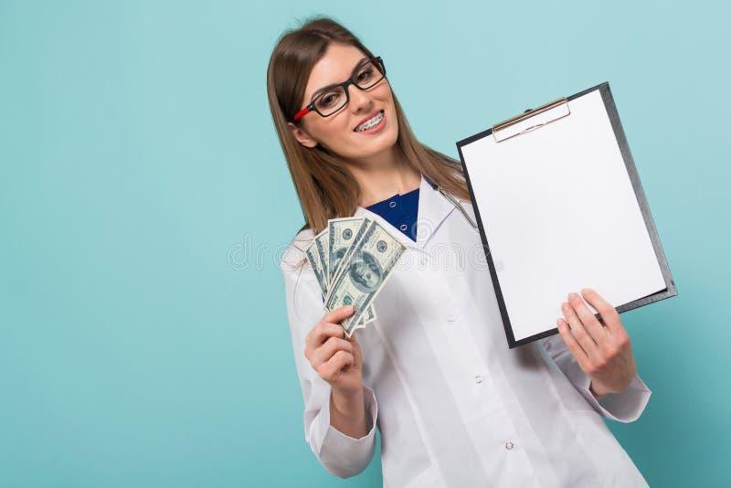 Женский доктор с вентилятором денег и доски сзажимом для бумаги стоковые фото
