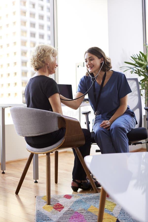 Женский доктор Wearing Scrubs В Офис слушая старший женский комод пациентов используя стетоскоп стоковые изображения rf