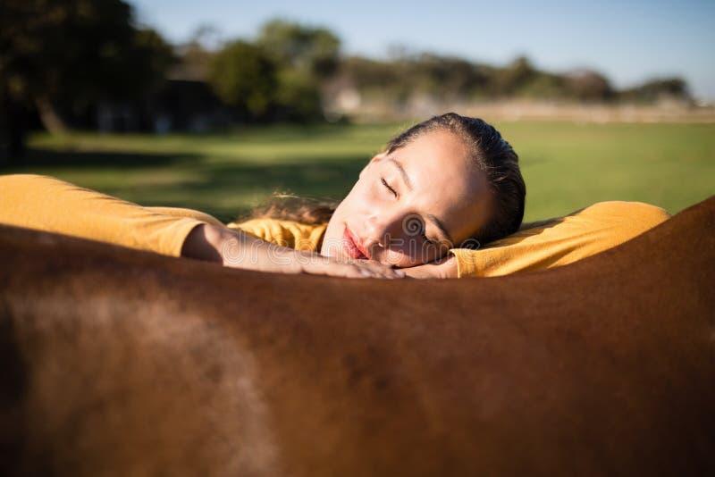 Женский жокей ослабляя на лошади на амбаре стоковые фотографии rf
