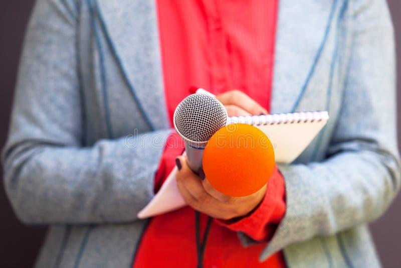 Женский журналист на пресс-конференции, пишущ примечания, держа микрофоны стоковое изображение