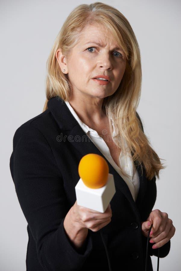 Женский журналист с микрофоном на белой предпосылке стоковые изображения