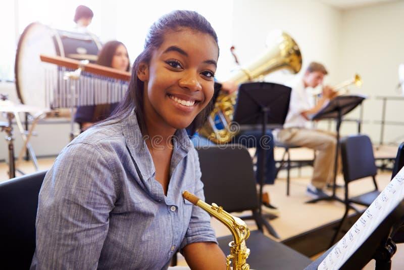 Женский зрачок играя саксофон в оркестре средней школы стоковые изображения