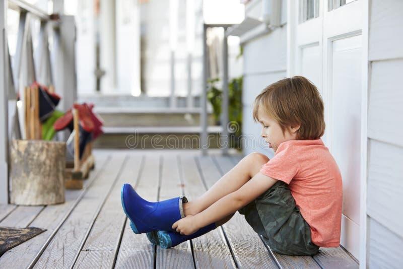 Женский зрачок на школе Montessori кладя на ботинки Веллингтона стоковые фотографии rf