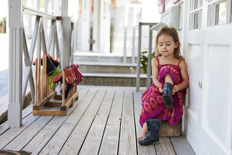 Женский зрачок на школе Montessori кладя на ботинки Веллингтона стоковые изображения