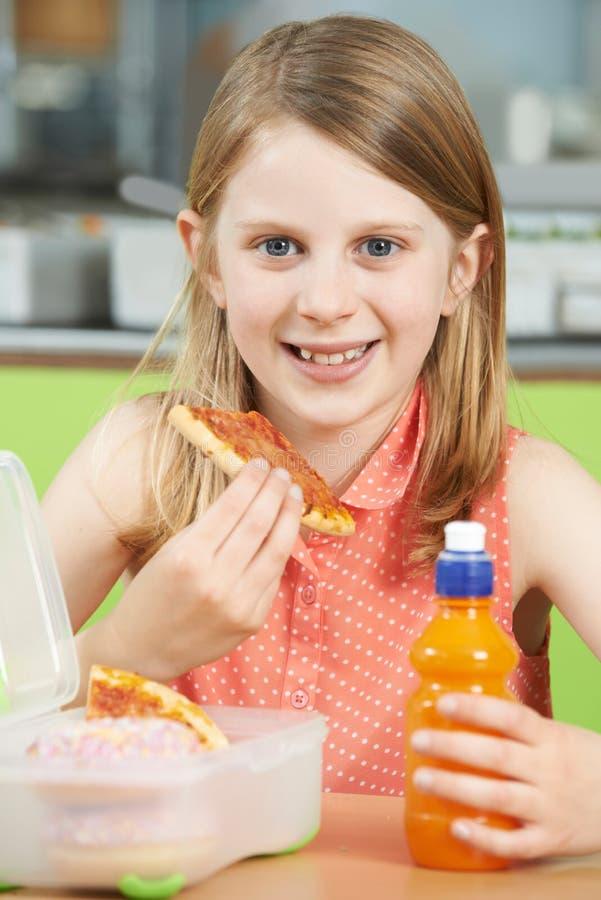 Женский зрачок сидя на таблице в еде Unhealt школьного кафетерия стоковое изображение
