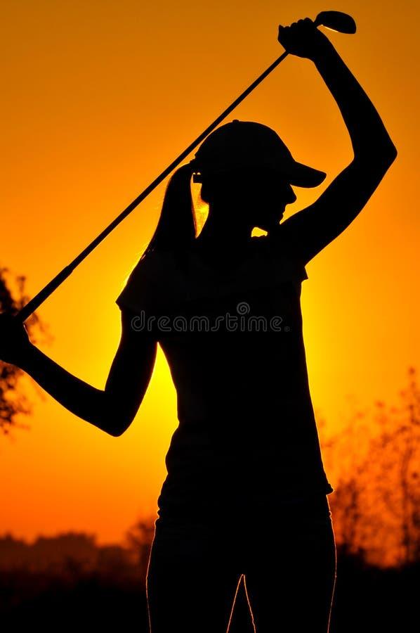 Женский игрок в гольф на восходе солнца стоковые фотографии rf