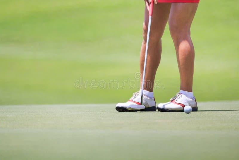 Женский игрок в гольф кладя на зеленый цвет стоковая фотография rf