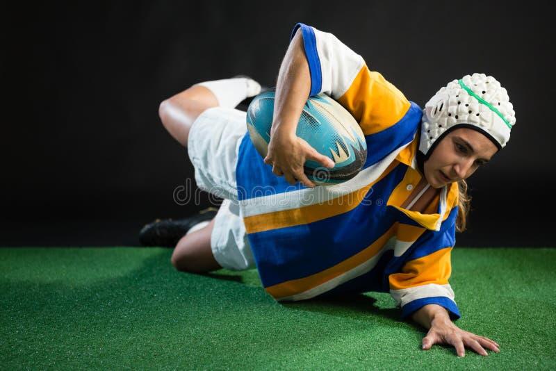 Женский игрок рэгби пытая касание вниз стоковое изображение rf