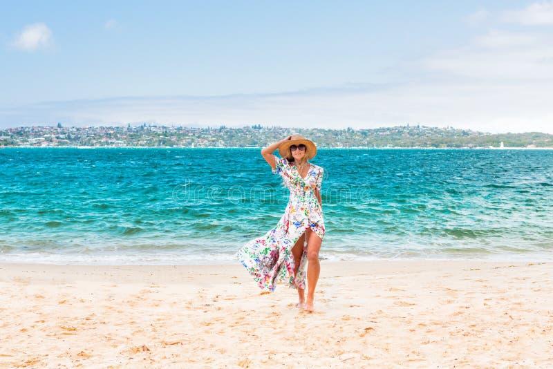 Женский идти вдоль уединенного пляжа в гавани Сиднея стоковые изображения