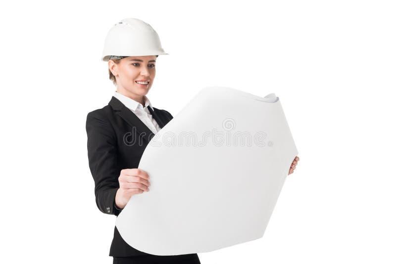 Женский инженер по строительству и монтажу в костюме смотря светокопию стоковые фотографии rf