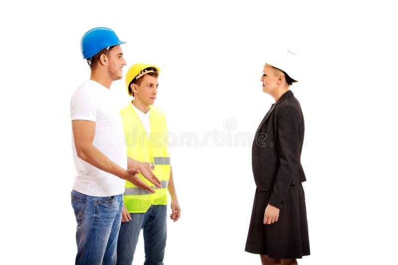 Женский инженер разговаривая с 2 построителями стоковая фотография rf