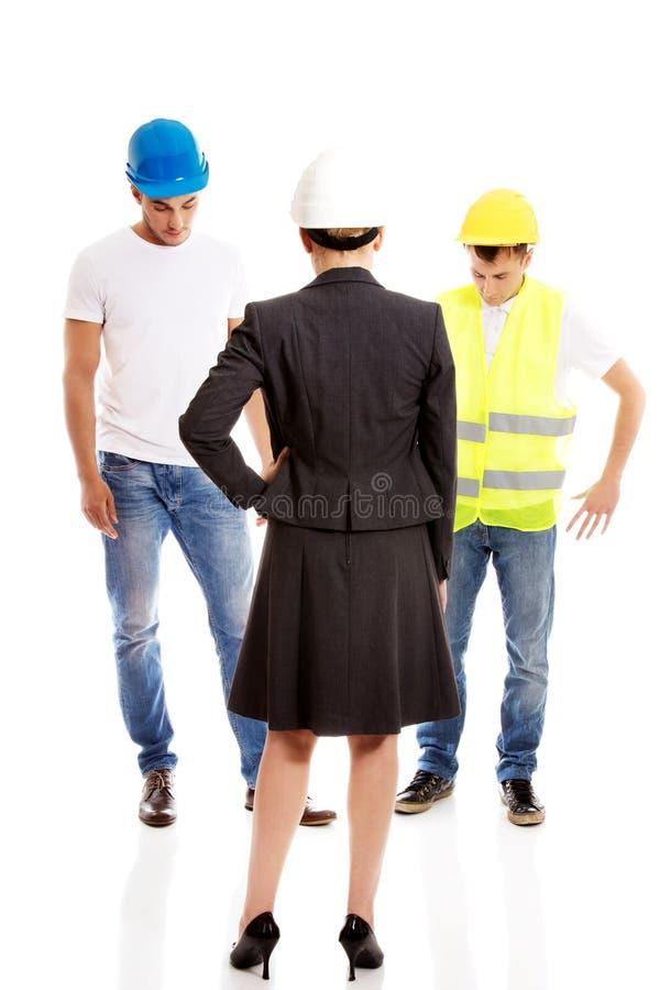 Женский инженер разговаривая с 2 построителями стоковое изображение rf