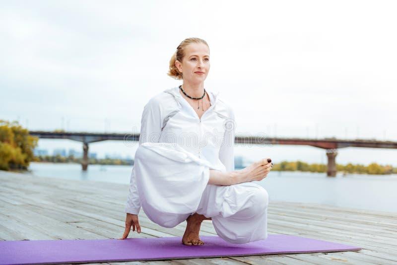 Женский инструктор йоги легко практикуя осложненные asanas стоковые фотографии rf