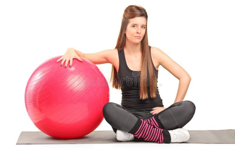 Женский инструктор фитнеса сидя на работая циновке стоковая фотография