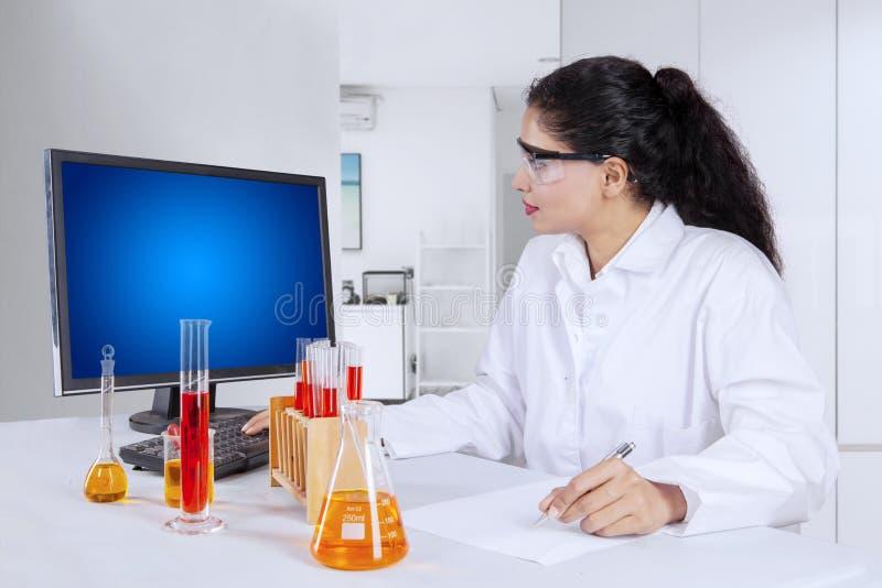 Женский исследователь используя компьютер в лаборатории стоковая фотография rf