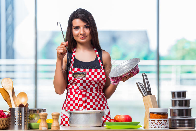 Женский кашевар подготавливая суп в ярко освещенной кухне стоковое фото