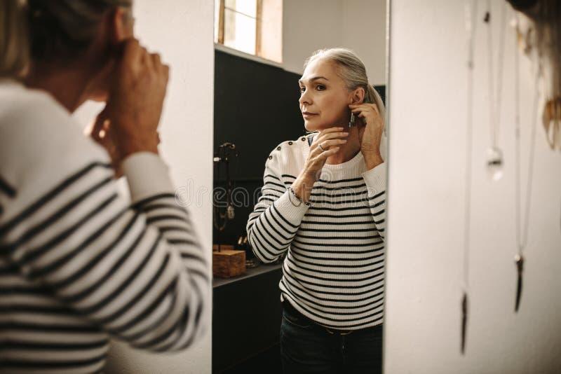 Женский клиент пробует дальше дизайнерскую серьгу на ювелире стоковое изображение
