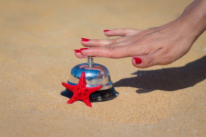 Женский колокол гостиницы отжимать руки на песчаном пляже стоковое изображение