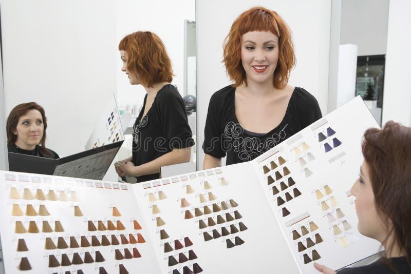 Женский клиент и парикмахер смотря диаграмму цвета стоковое фото