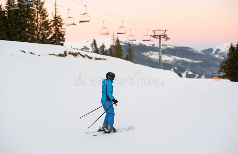 Женский лыжник на середине наклона лыжи против подъемов лыжи стоковая фотография rf