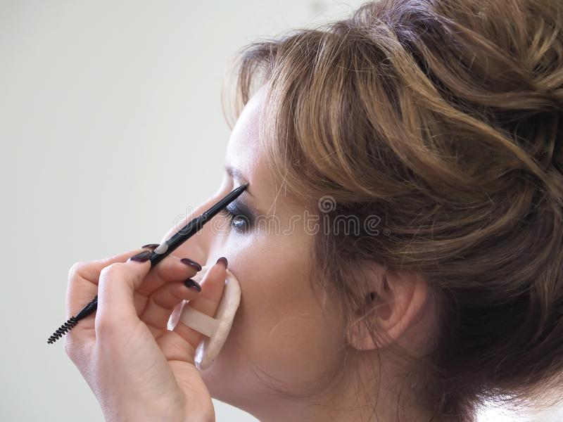 Женский макияж с карандашем брови конец вверх стоковые изображения rf