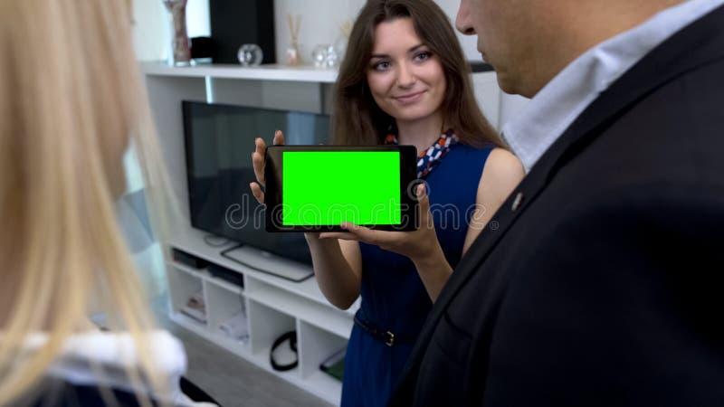 Женский маклер показывая зеленую таблетку экрана с app для умного управления дома стоковая фотография