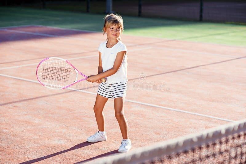 Женский маленький теннисист в практике белого спорта равномерной в ударять с ракеткой тенниса на тренировке на на открытом воздух стоковое фото