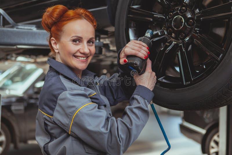 Женский механик работая на станции обслуживания автомобиля стоковое изображение rf