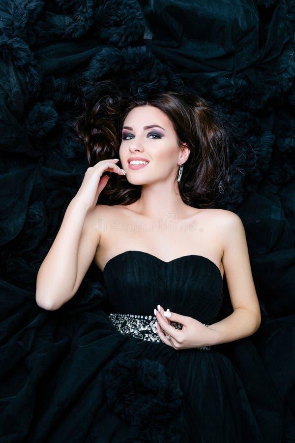 Женский модельный лежать в черном сексуальном платье стоковые фото