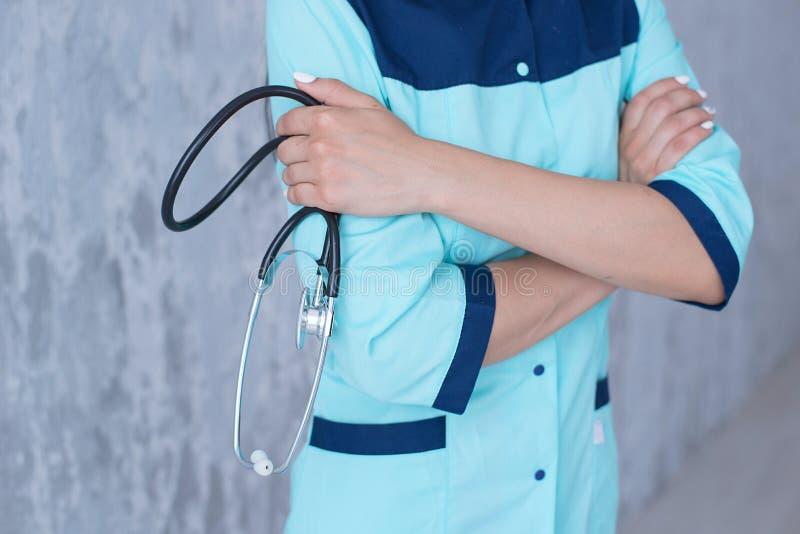 Женский доктор держа стетоскоп в его руке стоковая фотография