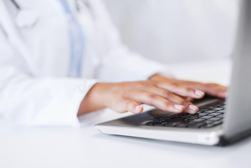 Женский доктор используя ее портативный компьютер