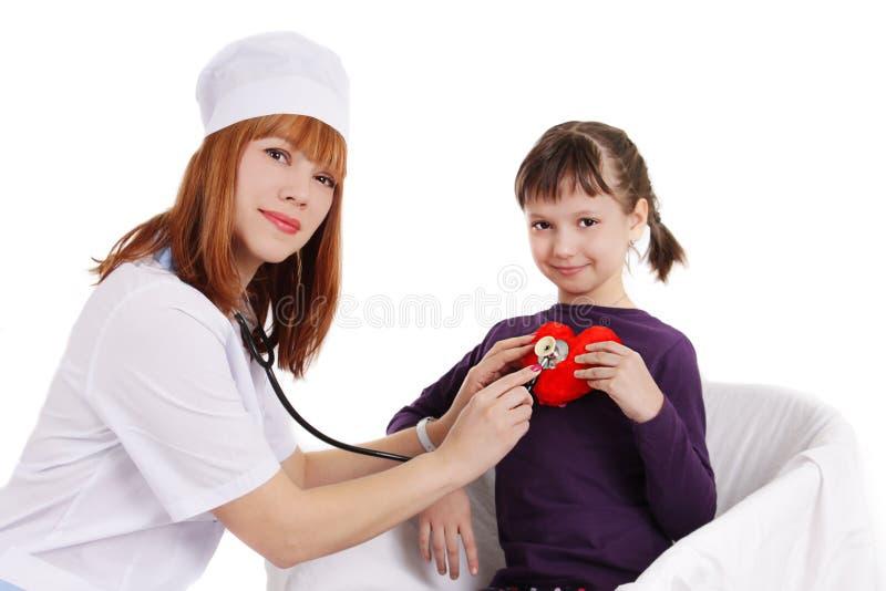 Download Женский доктор и маленькая девочка держа сердце плюша Стоковое Изображение - изображение насчитывающей backhoe, сердце: 40578053