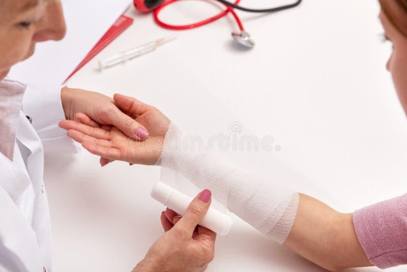 Женский доктор перевязывает руку стоковые фото