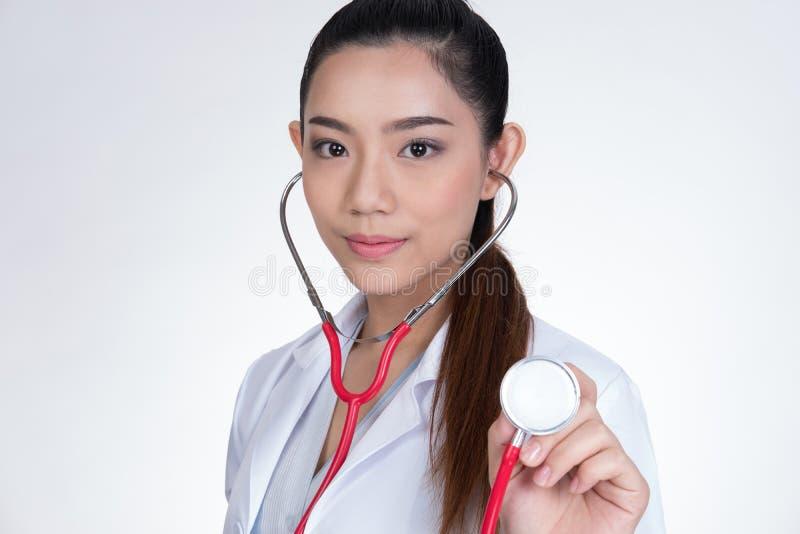 Женский доктор показывая стетоскоп для проверки над белым backgro стоковое фото