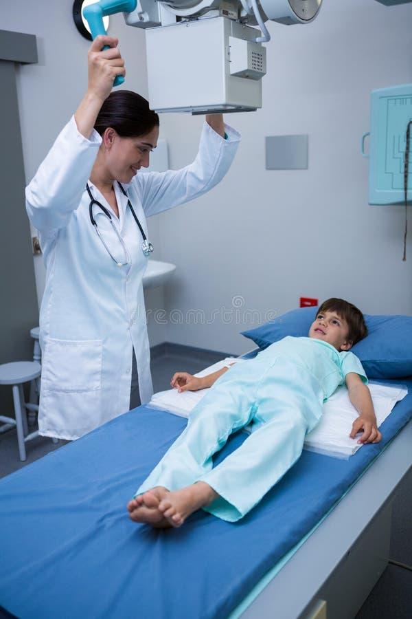 Женский доктор регулируя передвижной рентгеновский аппарат на пациенте стоковое изображение rf