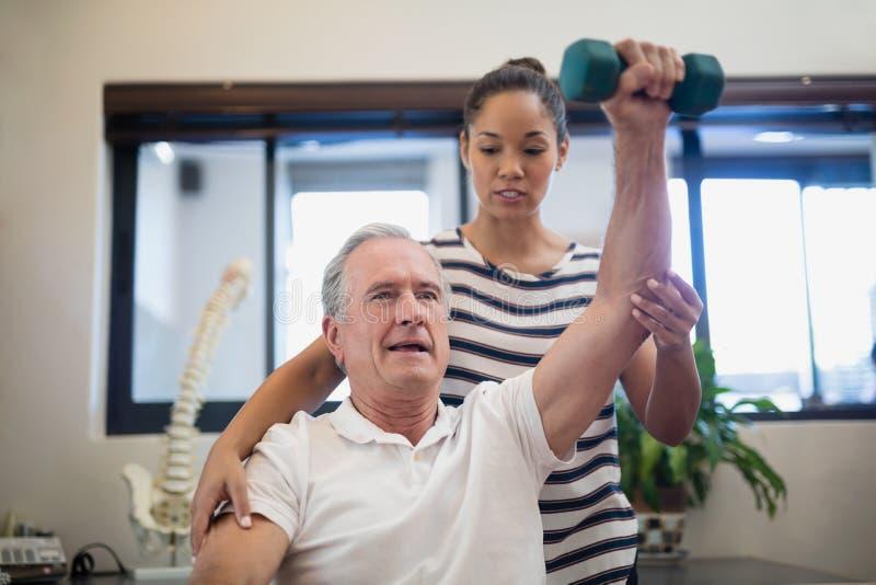 Женский доктор смотря старшую терпеливую поднимаясь гантель стоковая фотография rf