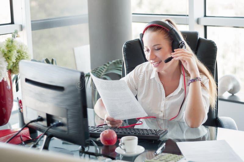 Женский оператор в центре телефонного обслуживания, работая в офисе стоковое фото rf