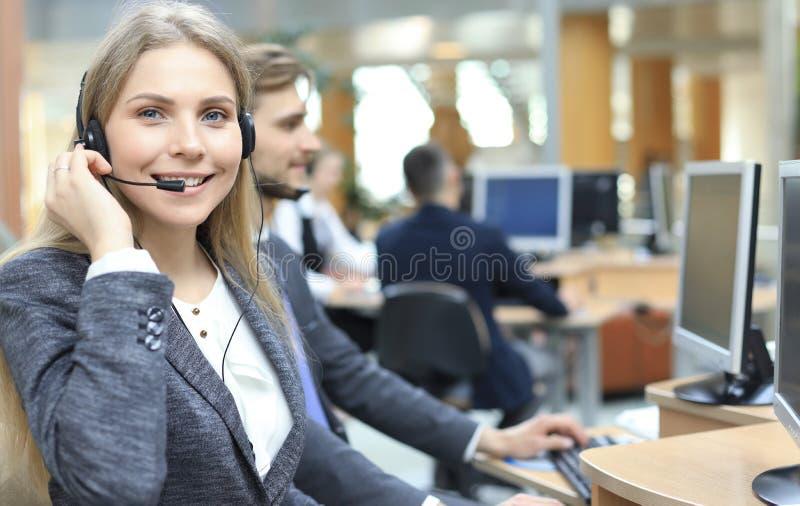 Женский оператор работы с клиентом со шлемофоном и усмехаться стоковые фото