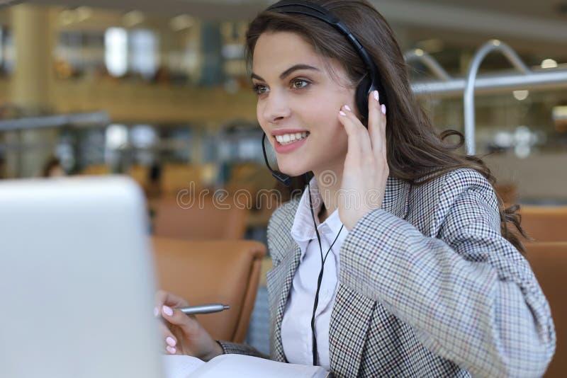 Женский оператор работы с клиентом со шлемофоном и усмехаться стоковая фотография