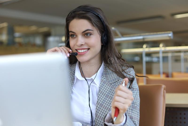 Женский оператор работы с клиентом со шлемофоном и усмехаться стоковое изображение