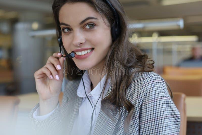 Женский оператор работы с клиентом со шлемофоном и усмехаться стоковое фото rf