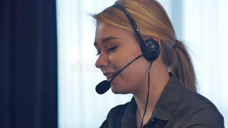 Женский оператор работы с клиентом с шлемофоном говоря и усмехаясь стоковые изображения rf