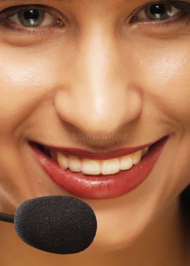 Женский оператор работы с клиентом с шлемофоном и усмехаться стоковая фотография
