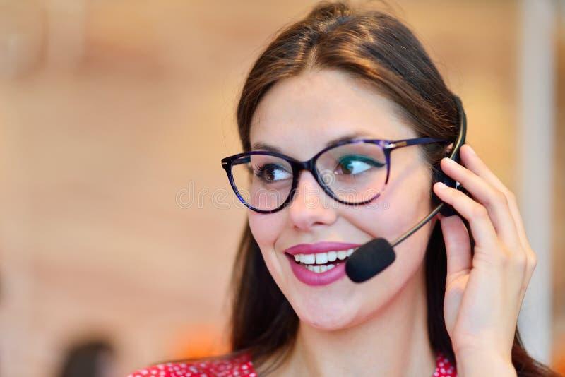 Женский оператор работы с клиентом с шлемофоном и усмехаться стоковые фото