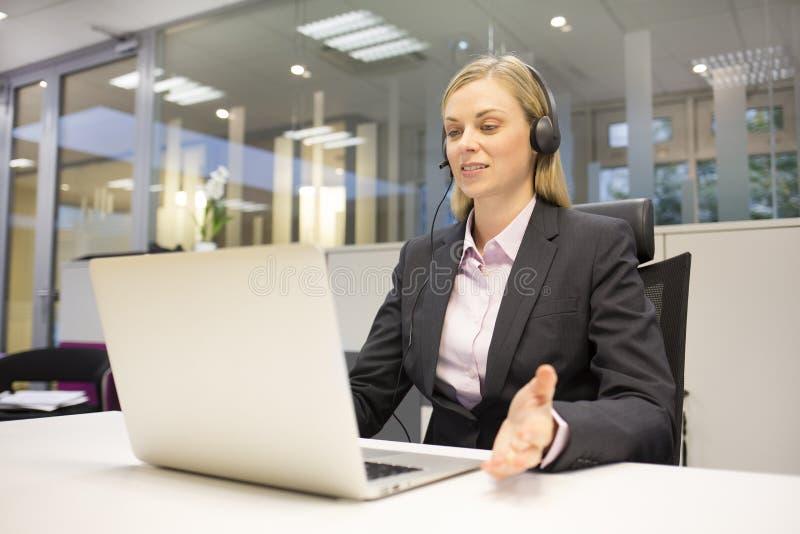 Женский оператор центра телефонного обслуживания беседы дела стоковые изображения