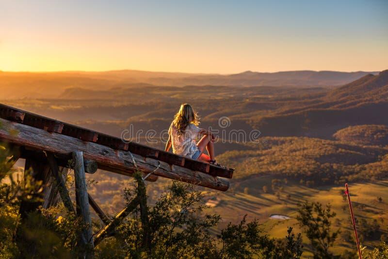 Женский ослаблять на Mt Blackheath наблюдая золотой солнечный свет от деревянной платформы стоковые изображения rf