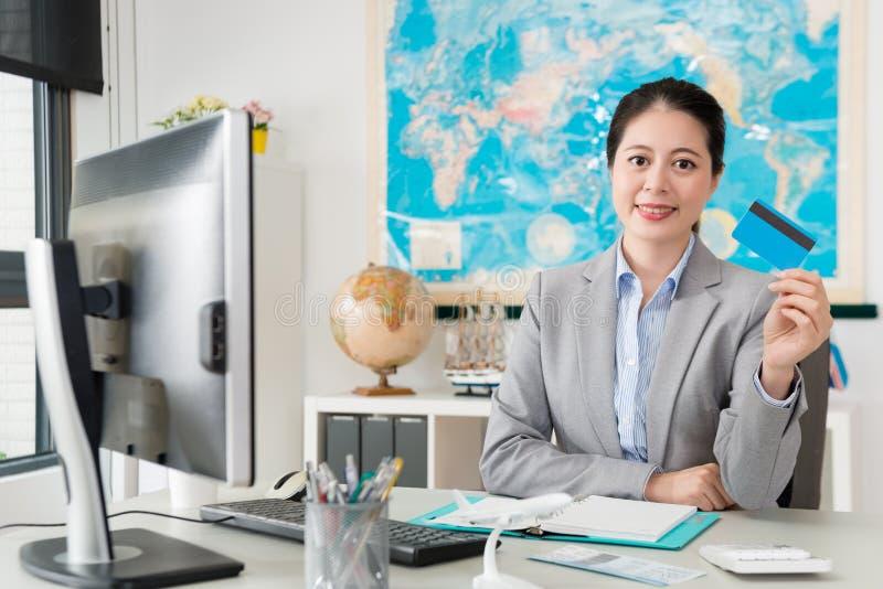Женский офис агента по путешествиям показывая кредитную карточку стоковые изображения
