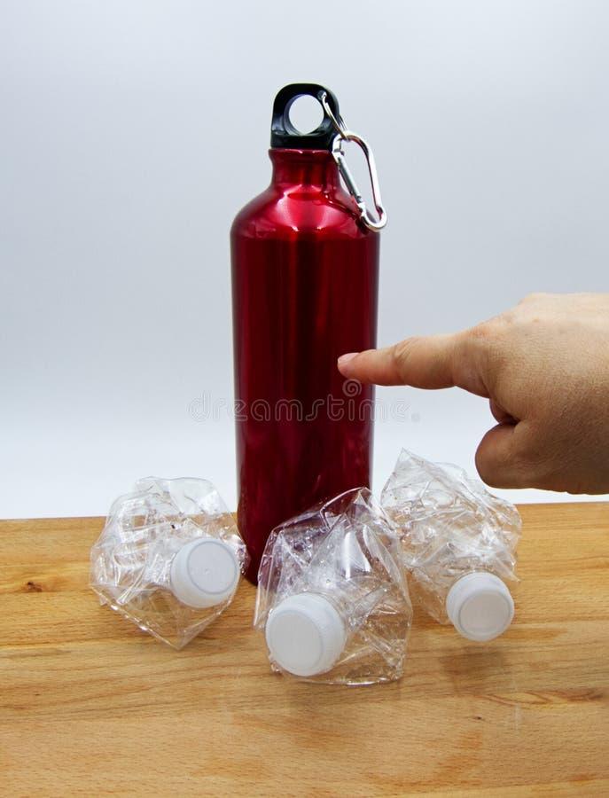 Женский палец руки указывая красная современная бутылка с водой затем 3 crusched пластиковые бутылки Концепция повторного пользов стоковые изображения