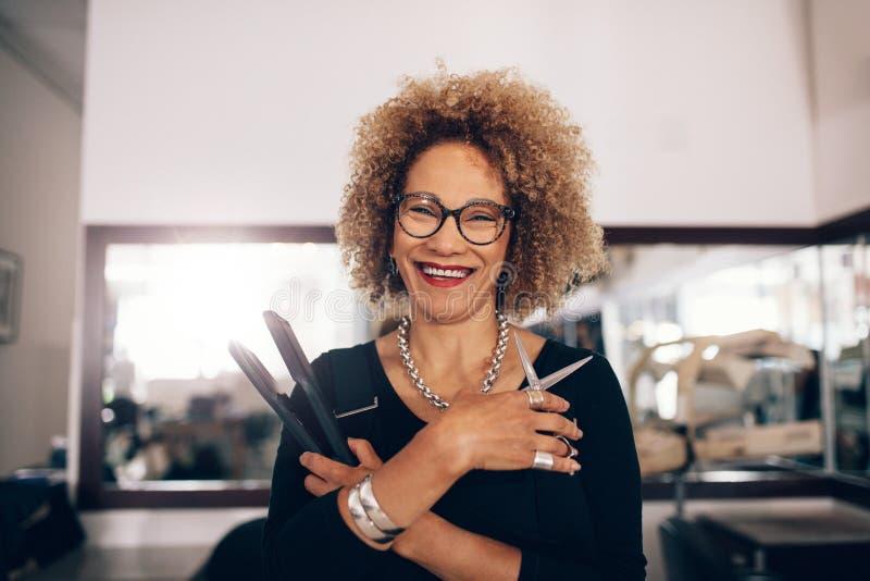 Женский парикмахер на салоне держа аксессуары парикмахерских услуг стоковые изображения rf