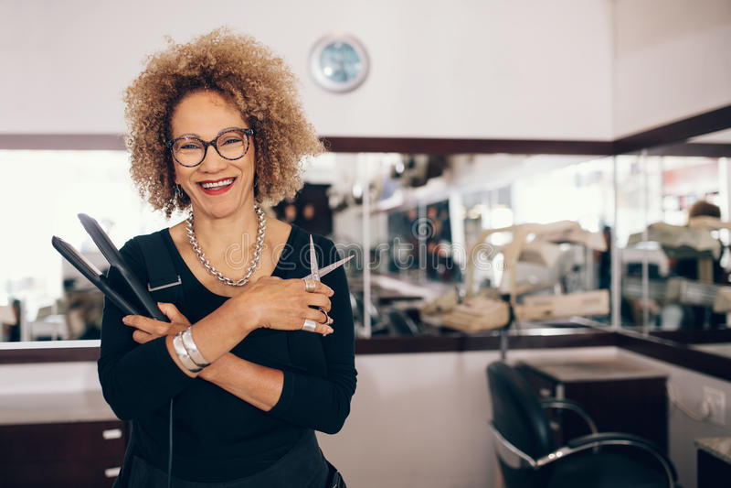 Женский парикмахер на салоне держа инструменты парикмахерских услуг стоковые изображения
